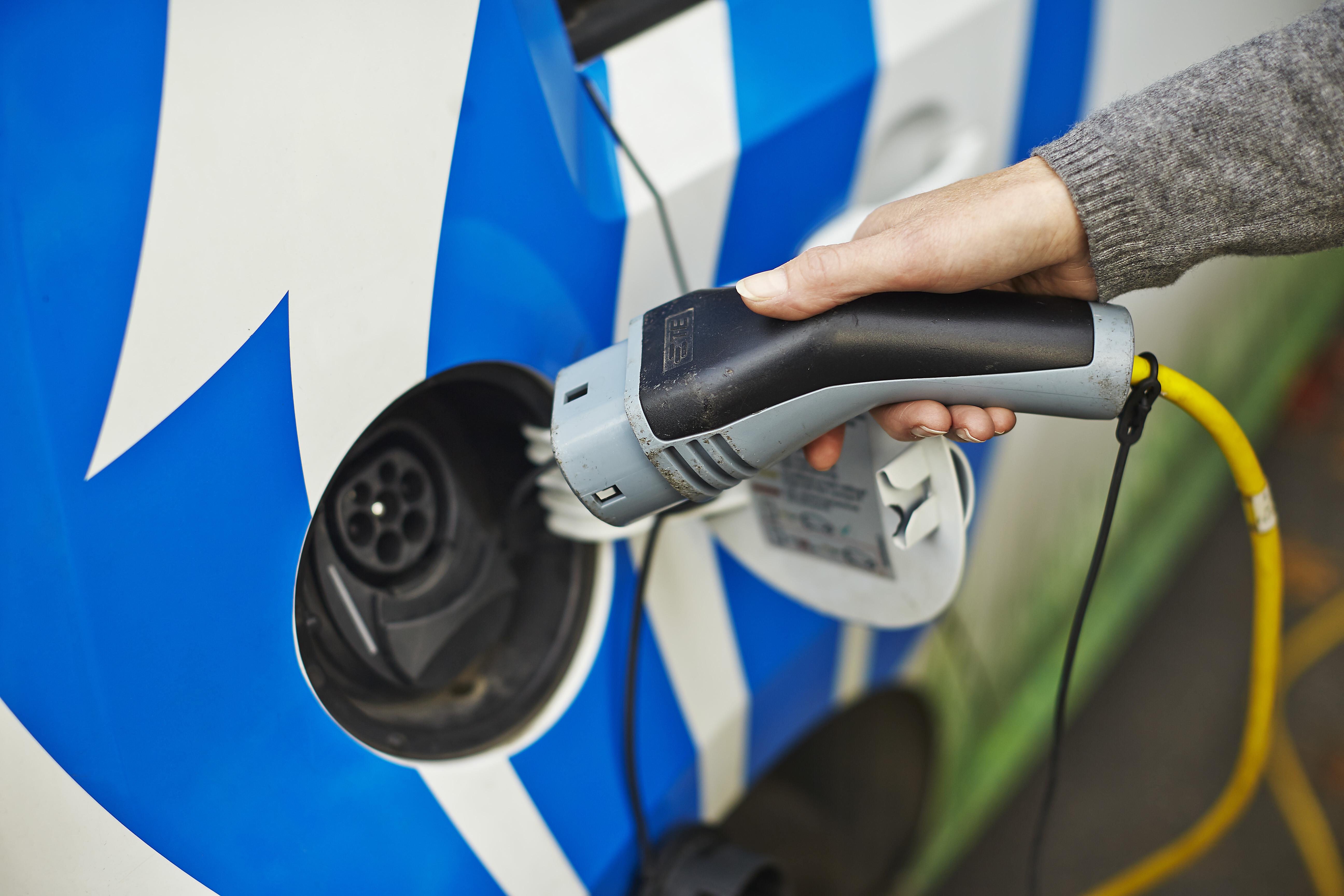 Person som er i ferd med å stikke elbil kontakten i bilen for å begynne å lade