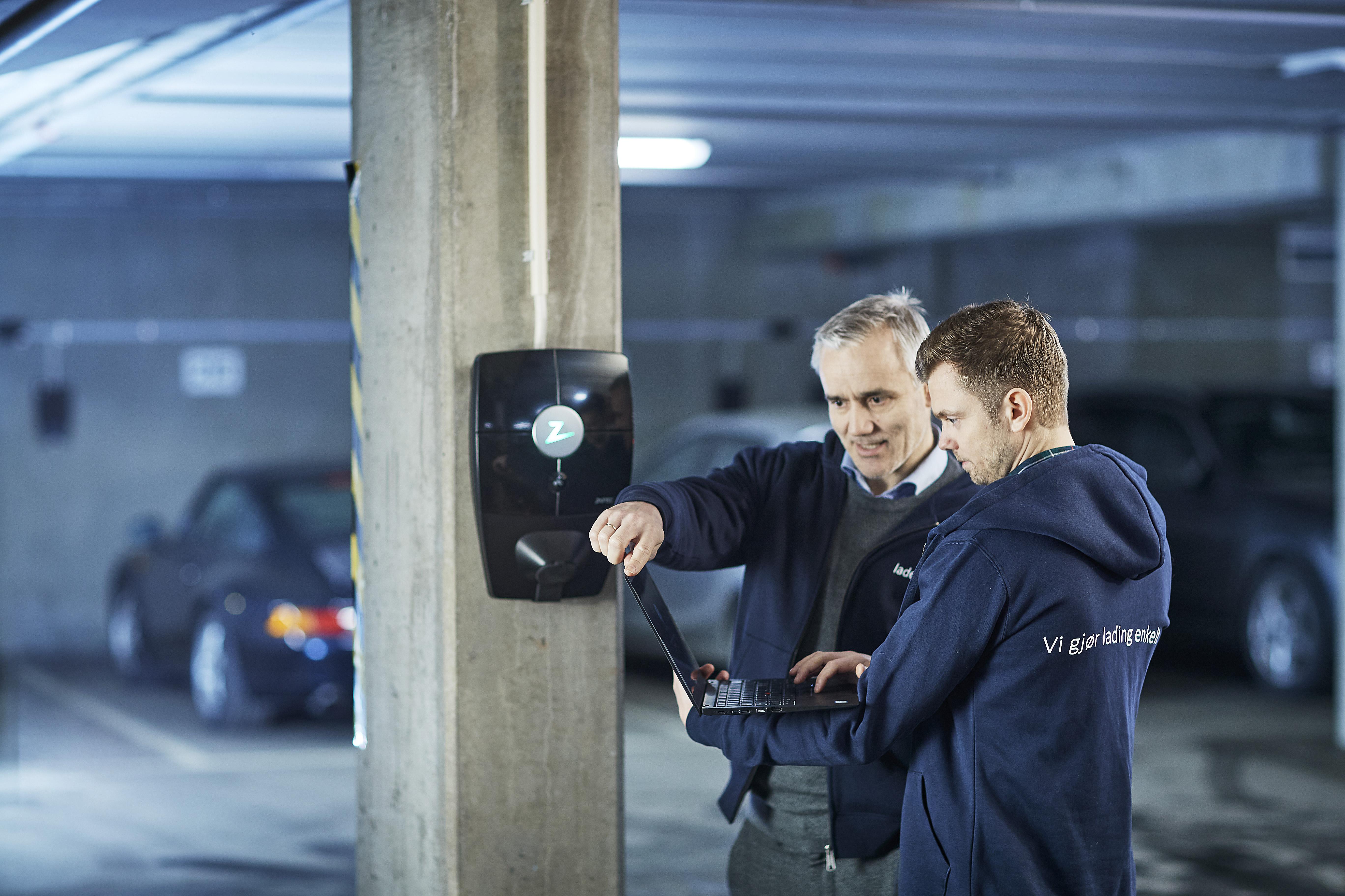 To Ladeklar installatører som kontrollerer en ladeboks i en garasjekjeller